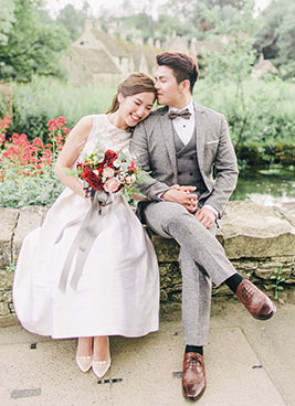 bride and groom sit on wall in the cotswolds