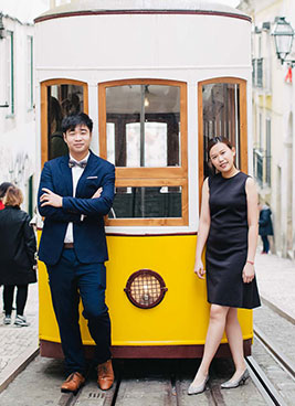 couple stand in front of lisbon tram