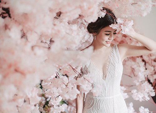 bride poses next to pink cherry blossoms