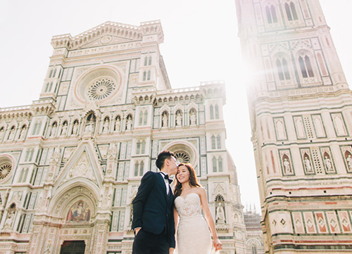 groom kisses bride during sunset in florence