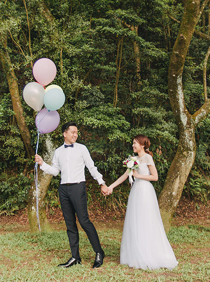 couple walking holding balloons during a photo shoot in the cotswolds