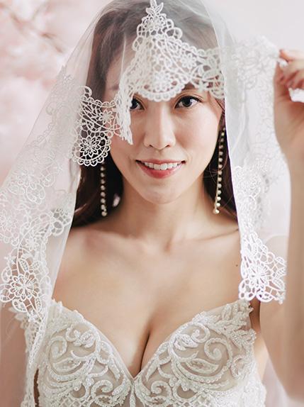 bride smiles covered in veil