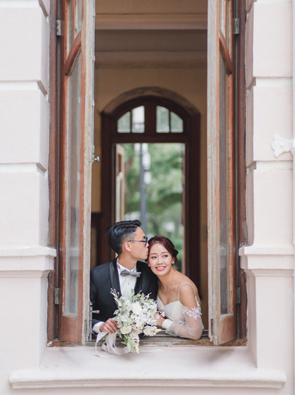 couple posing in window during pre wedding photography shoot