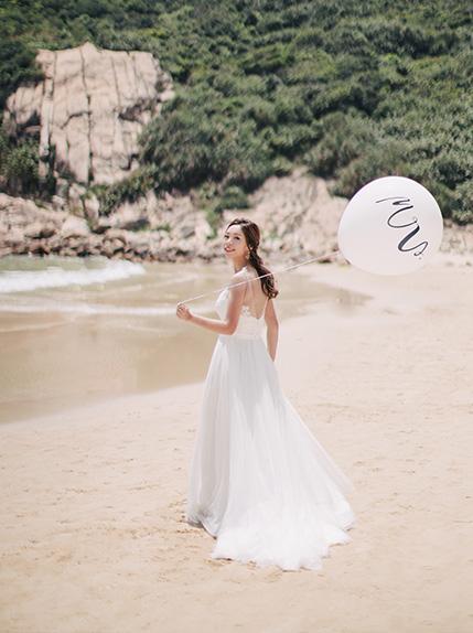 bride walks on beach holding wedding balloon