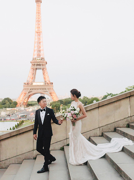 couple posing on stairs in front of eiffel tower