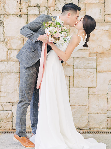 groom kisses bride during photoshoot
