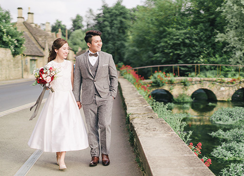 couple walking through burton on the water with bridge in background
