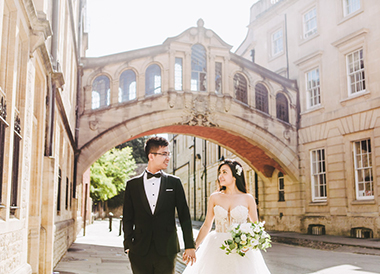 couple pose in front of traditional architecture