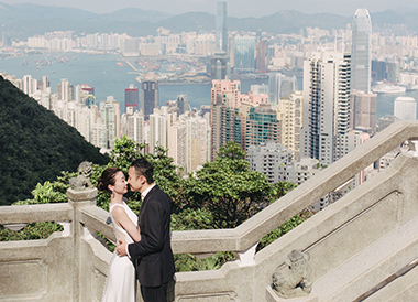 couple pose during pre wedding shoot with hong kong skyline in background