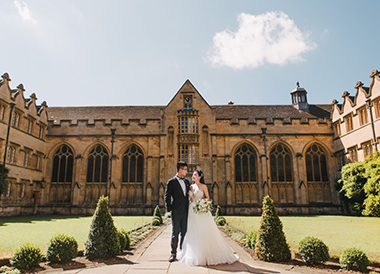 couple pose in front of oxford school