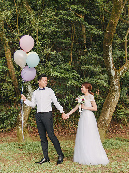 bride and groom walk holding hands with groom showing balloons