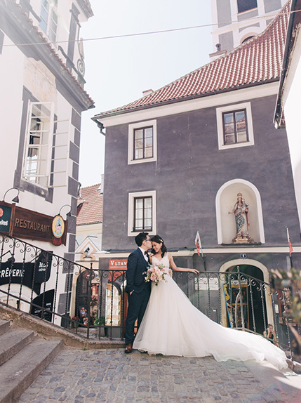 couple kiss with rustic european style buildings in background