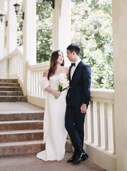 couple smiling in white wedding dress and black suit