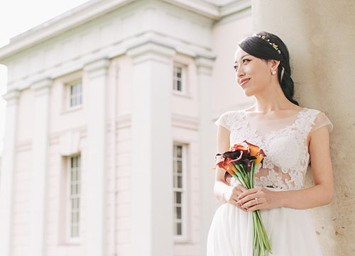 bride leans against wall smiling with bouquet