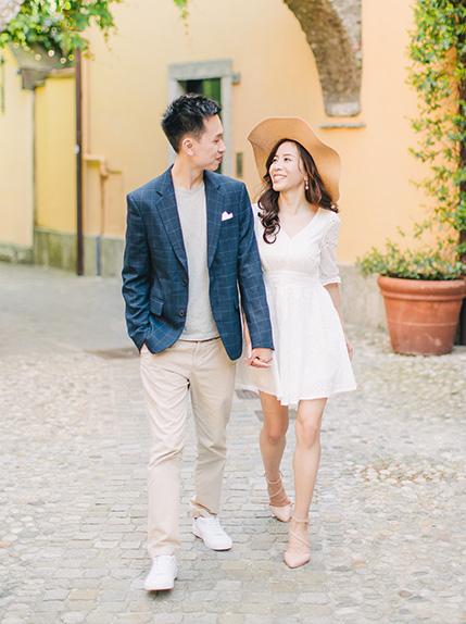 bride smiles at groom walking during photoshoot