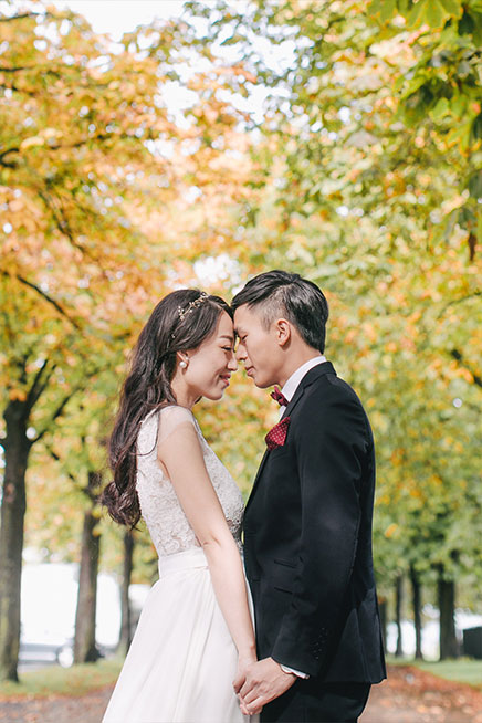 couple smiles during photoshoot surrounded by autumn trees