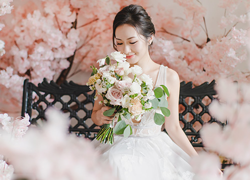 bride holds bouquet while sat on bench next to sakura tree