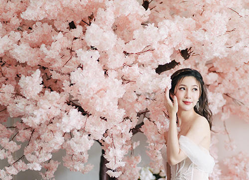 bride poses in gown while having cherry blossom photoshoot