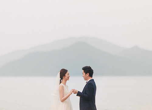 bride and groom holding hands with sea in background