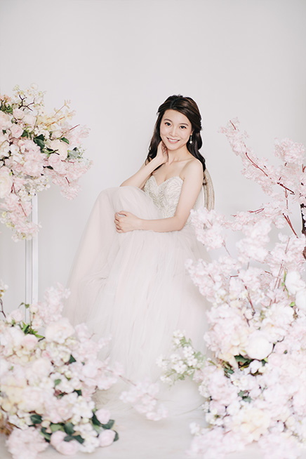 bride smiles surrounded by soft pink sakura cherry blossom