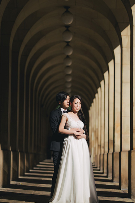 bride and groom posing in London archway