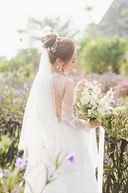 bride posing on path holding bouquet in sunlight