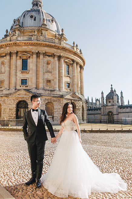 bride and groom pose in front of oxford city