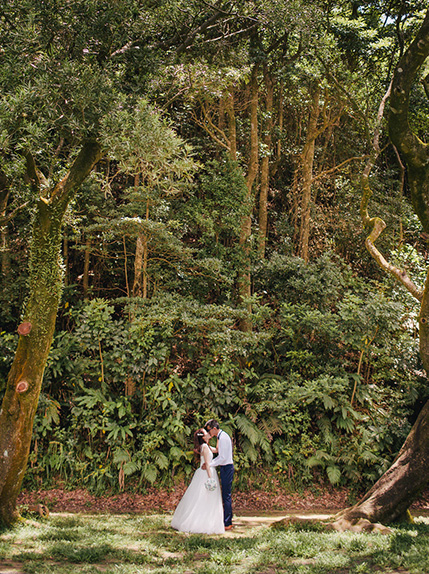 couple kissing in wedding attire surrounded by trees