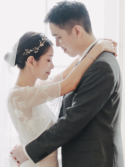 married couple backlit in veil with groom