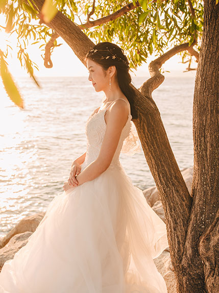 sunset photo with bride standing by tree next to water