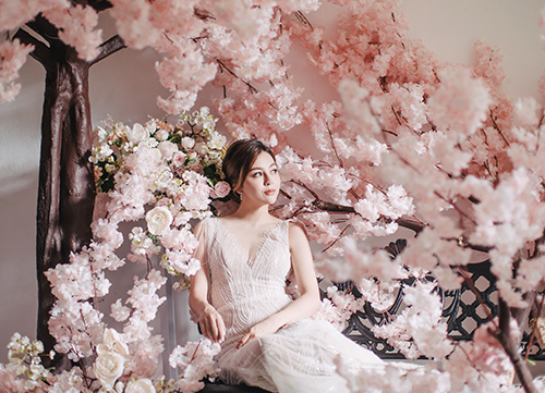 bride sits on a bench infront of sakura blossom tree