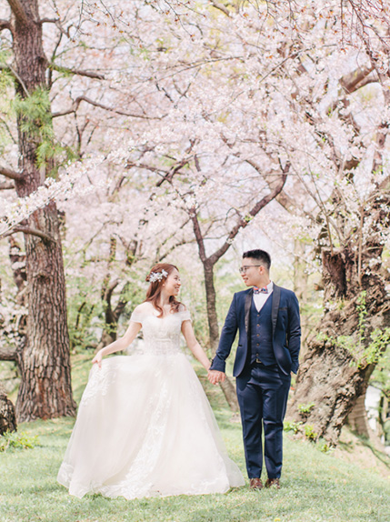 couple dancing surrounded by japanese cherry blossoms