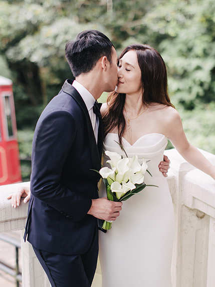 happily married couple kissing by white wall