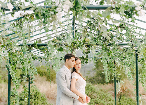 couple hugging surrounded by greenery
