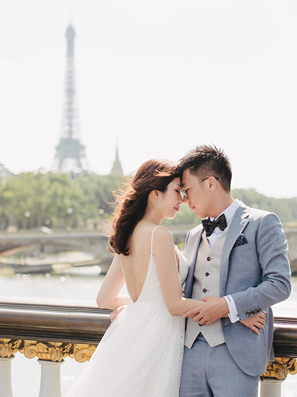 bride and groom pose during Paris pre wedding shoot with eiffel tower in scene