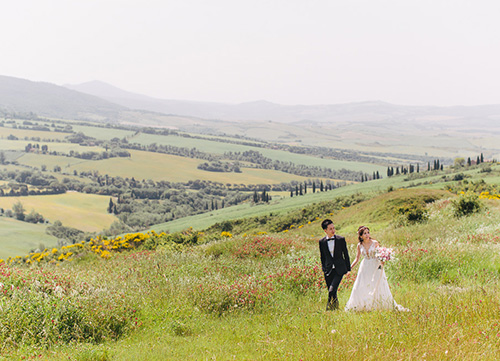 bride and groom walking in long grass in wedding suit and wedding gown
