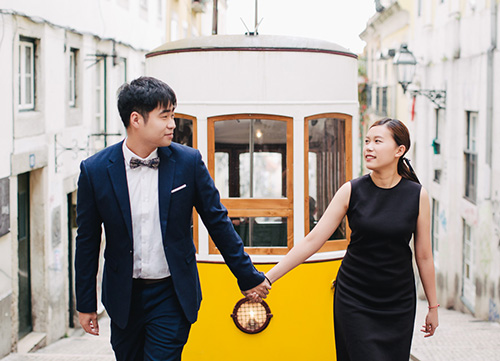 bride and groom in front of lisbon trams during pre wedding