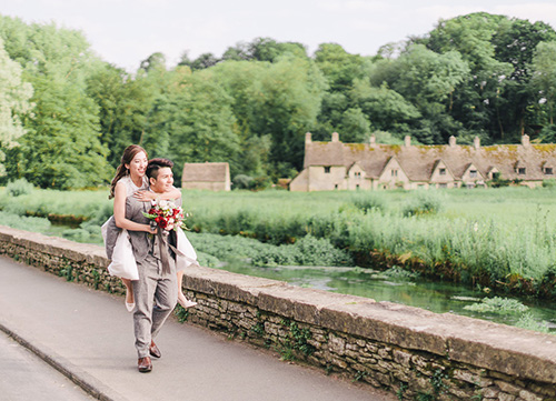 bride piggy backing on grooms back through street in the cotswolds