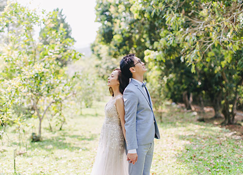 bride and groom stand back to back wearing wedding gown and blue suit