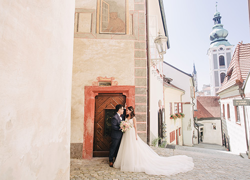 couple poses against wooden door on cobbled street