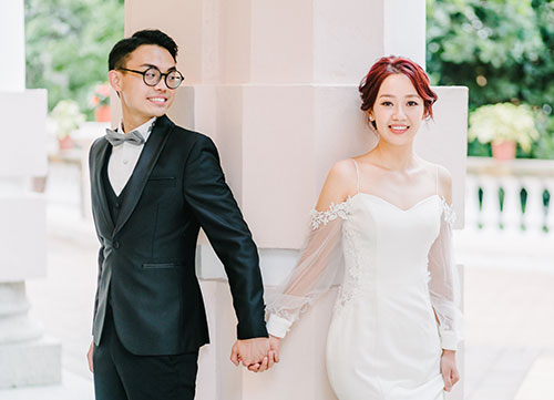 bride and groom holding hands stood next to pillar