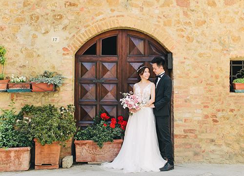 couple in wedding gown and suit poses during photoshoot in orrido di bellano