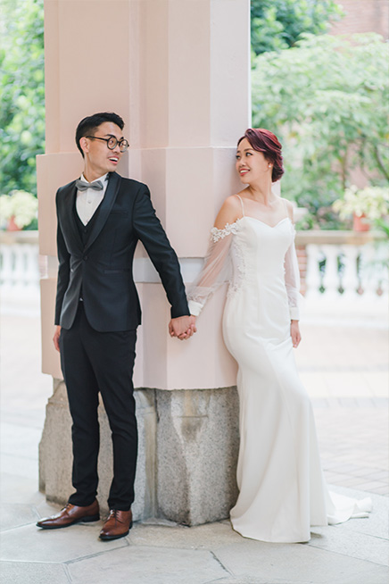 couple leaning against column smiling for photo