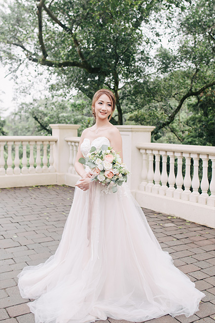 bride hold wedding bouquet while posing for wedding photo