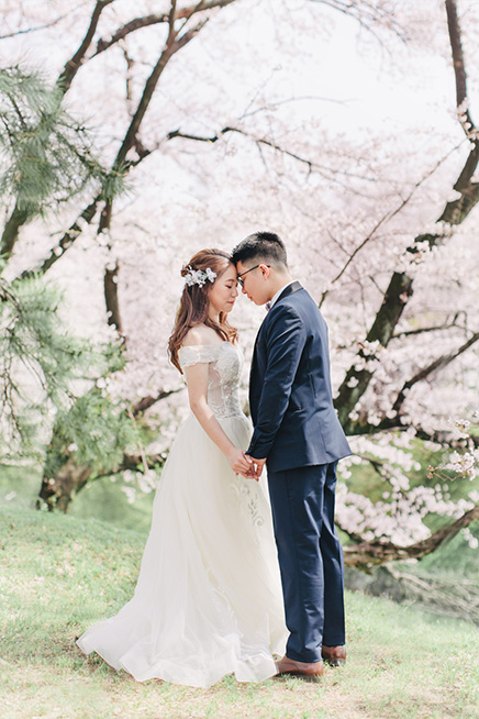 bride and groom pose underneath cherry blossom trees