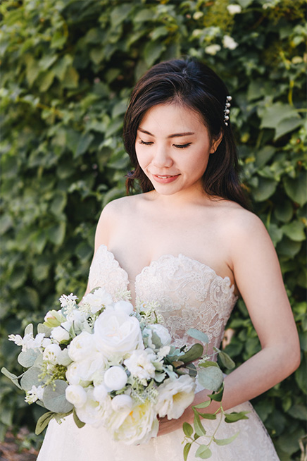 bride smiles while viewing her wedding bouquet