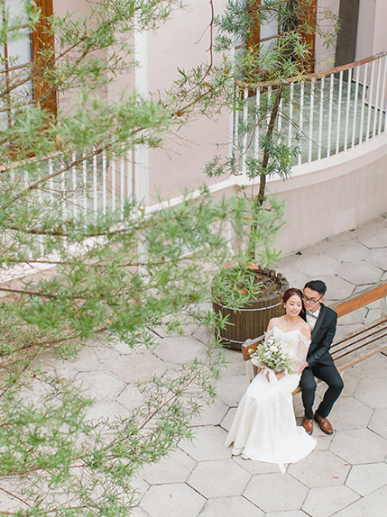 married couple posing on chair surrounded by pink building