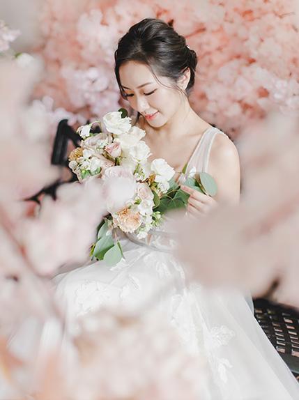 bride hidden by cherry blossom petals