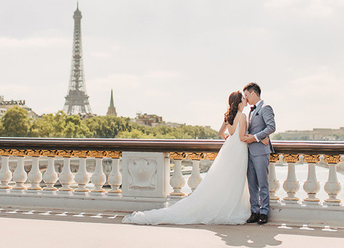 couple poses on pont alexandre iii bridge with eiffel tower in background