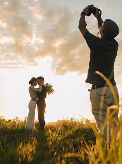 photographer takes photo of bride and groom and sunset